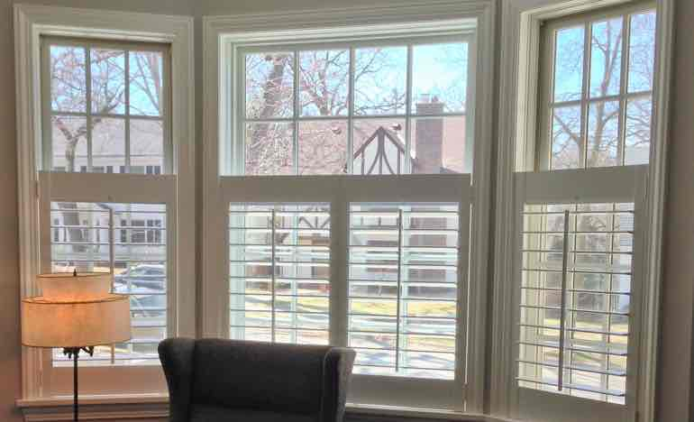 Bottom half white shutters in family room bay window.
