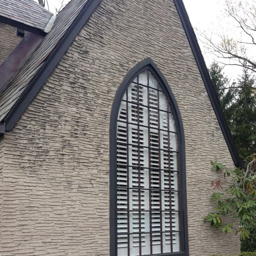 outside face of stone home with plantation shutters