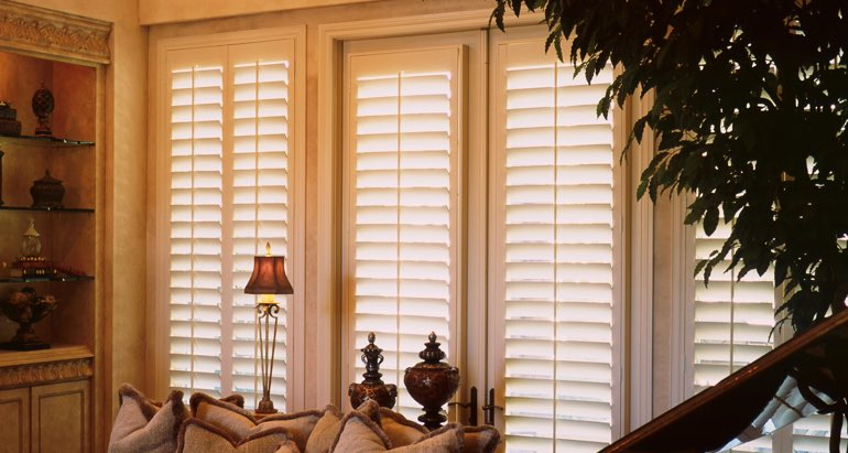 Plantation shutters on windows and door in Raleigh parlor