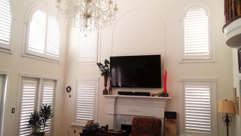 Raleigh great room with wall-mounted TV and arched windows.
