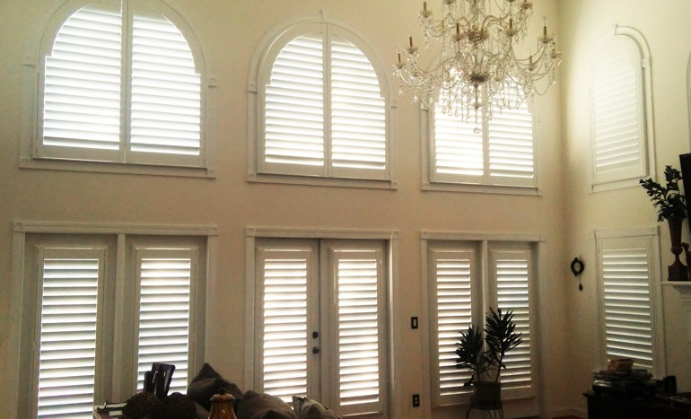 TV room in two-story Raleigh house with plantation shutters on tall windows.