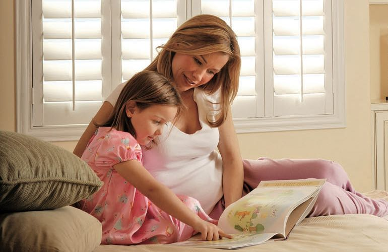 Mother and child reading on bed with shuttered windows.