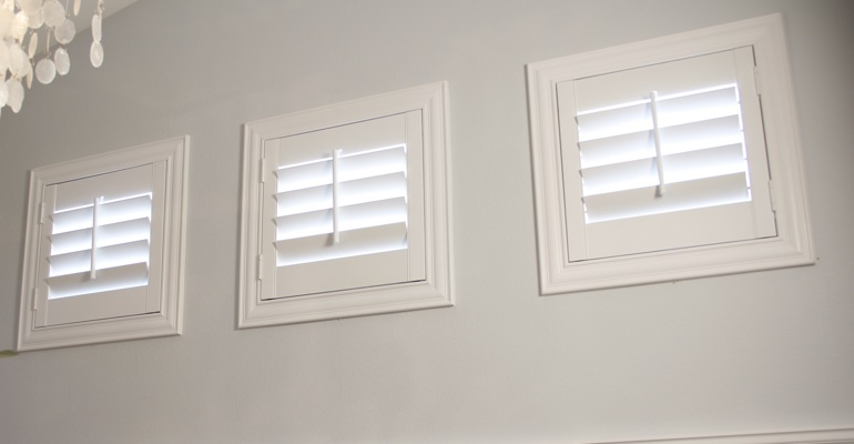 White shutters on square windows in laundry room