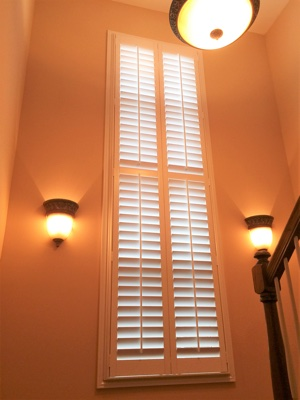Polywood plantation shutters in brightly lit stairwell.