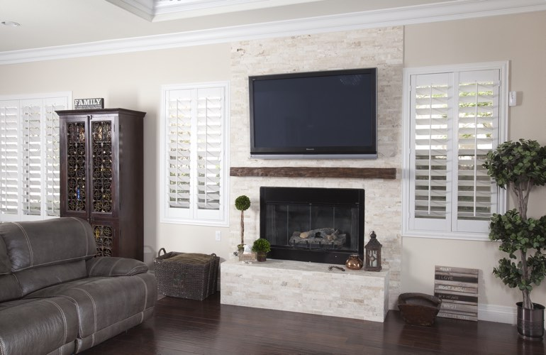 White plantation shutters in a Raleigh living room with plank hardwood floors.
