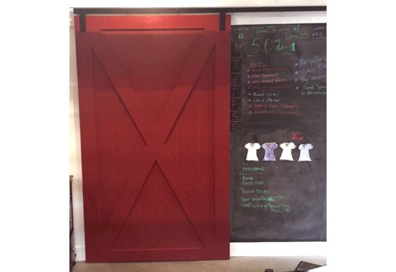 Bright red barn door with black track next to chalkboard