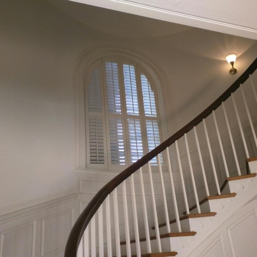 White plantation shutters covering arched window located in round stairwell.