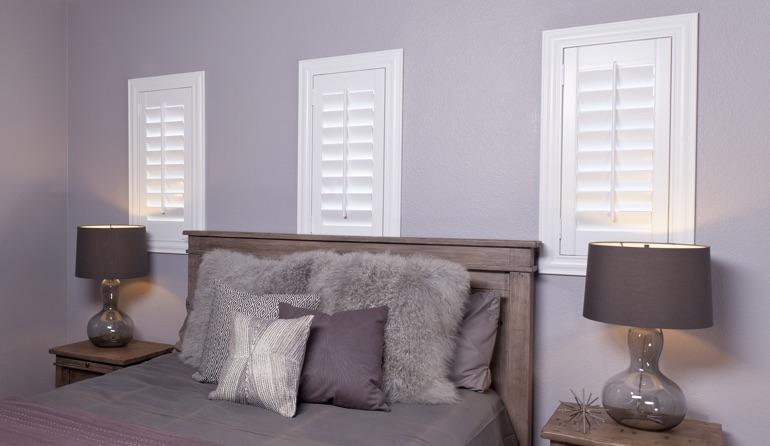White plantation shutters in Raleigh bedroom windows.